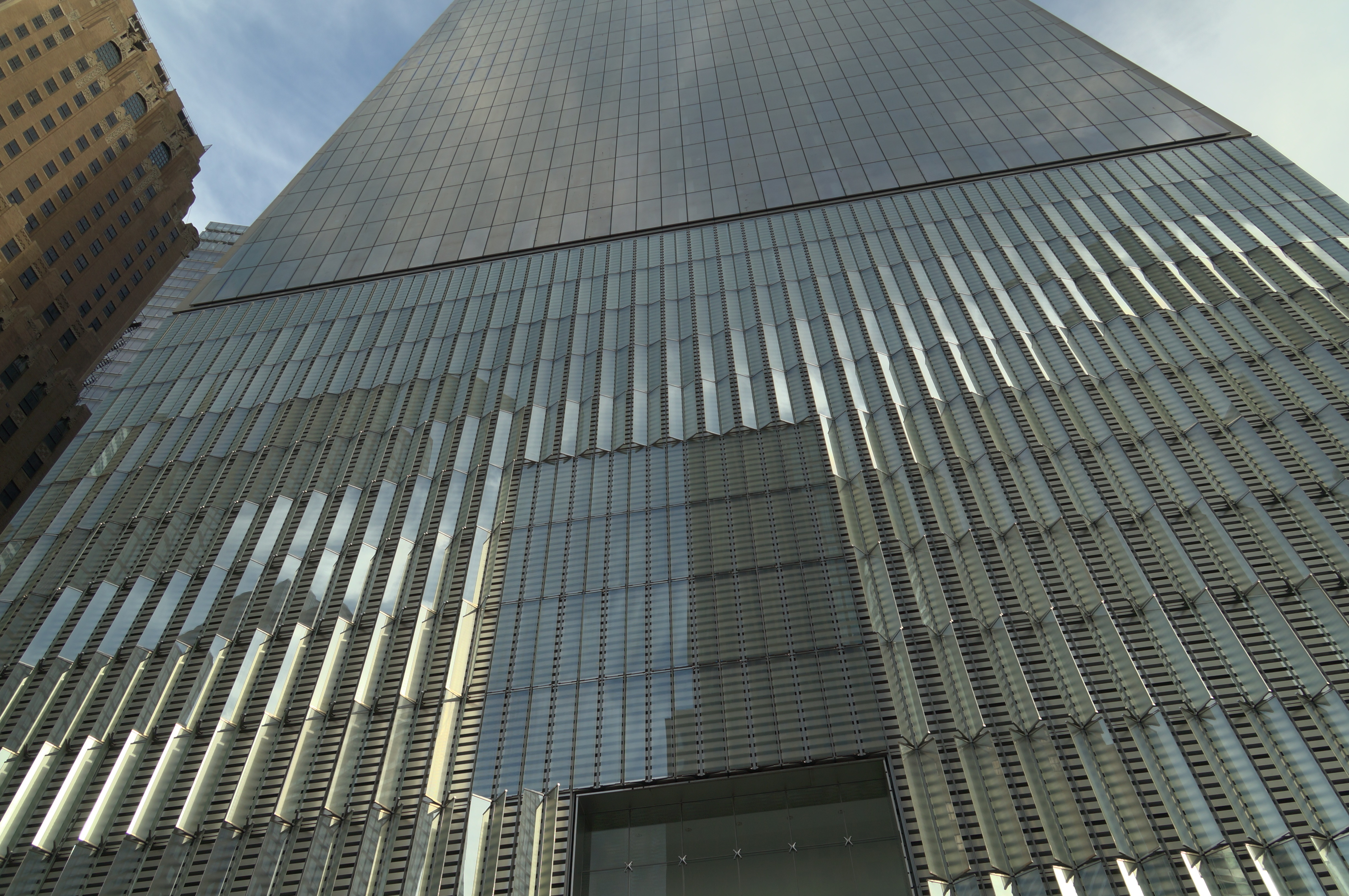 Angled glass fins protrude from stainless steel panels on the 185-foot tall concrete base of One World Trade Center. This base houses mechanical equipment and is designed to protect the building against ground-level explosions. (Lee Powell/TWP)